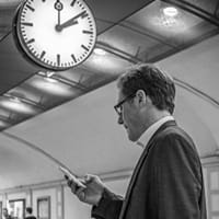 Man with phone near clock